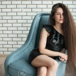 Cute Pretty Girl With Long Hair Sitting In A Chair With Her Legs