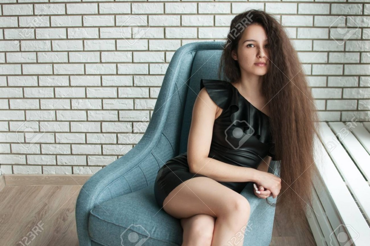 cute pretty girl with long hair sitting in a chair with her legs..