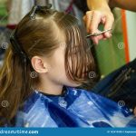 Hairdresser Making A Hair Style To Cute Little Girl Stock Photo Little Girl Long Haircuts With Bangs